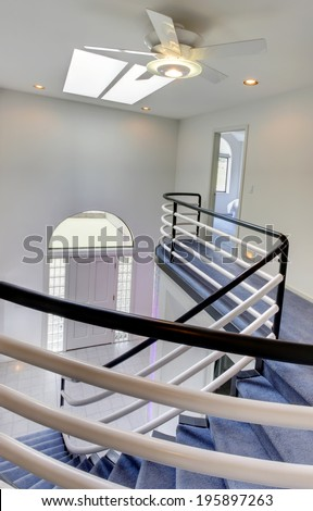 Entrance hall view from spiral staircase. Modern house interior - stock photo