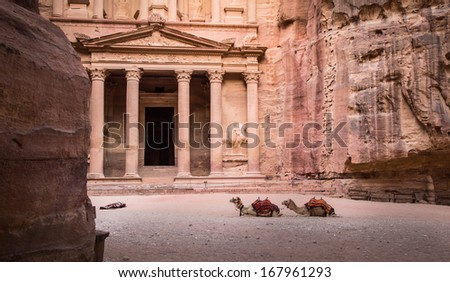 Entrance in City of Petra with two camells and sleeping bag on floor - stock photo