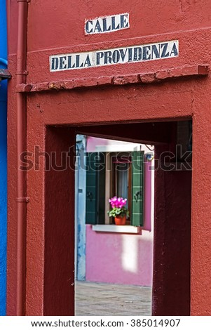 Entrance in one small street on Burano, Italy, with name Calle Della Providenza. Burano is an island with colorful architecture in the Venetian Lagoon. - stock photo