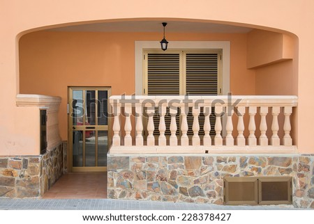 Entrance into the house with balcony. - stock photo