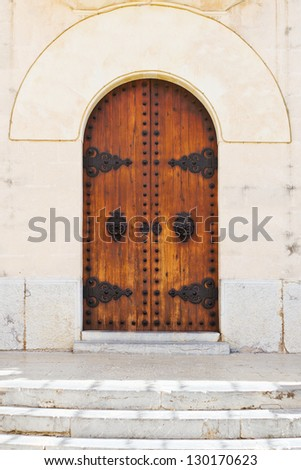 Entrance of a historical church with ornaments and wooden old doors - stock photo