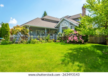 Entrance of a luxury house with a patio and beautiful landscaping on a bright, sunny day. Home exterior. - stock photo