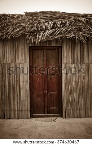 Entrance of traditional islamic home. Wall and roof cladded with natural dry palm leaves. - stock photo
