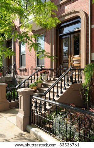 Entrance of Victorian house in Boston. Elegant steps, porch and front door framed by flower pots. - stock photo