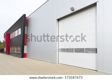 entrance of warehouse with office unit next to it - stock photo