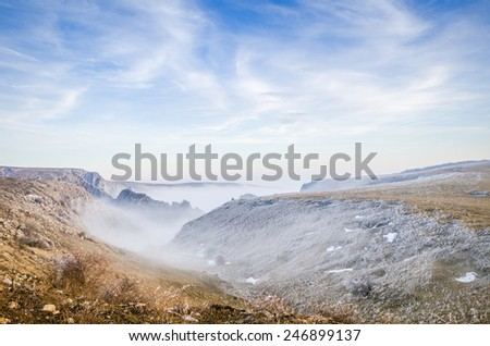 Entrance to a foggy valley with mist on a cold autumn-winter day with a blue sky and deserted landscape - stock photo