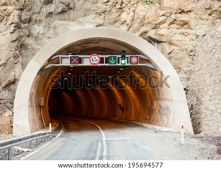 Entrance to a road tunnel with traffic signs - stock photo