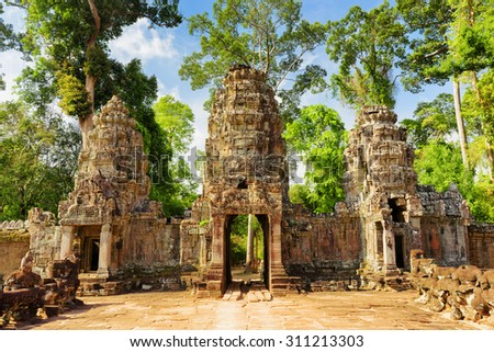 Entrance to ancient Preah Khan temple in Angkor, Siem Reap, Cambodia. Mysterious gopura on woods background. Angkor is a popular tourist attraction. - stock photo