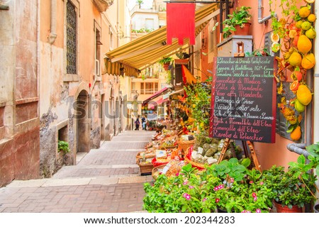 Entrance to local shop in Taormina, Sicily. Writing on the black table lists itmes on promotion. - stock photo