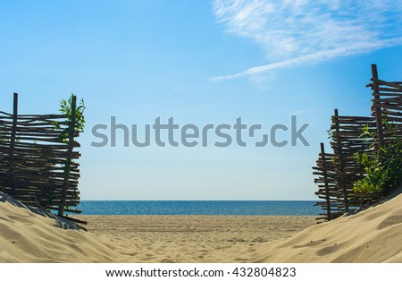 entrance to the beach over sand dunes made by woven wood branches - stock photo