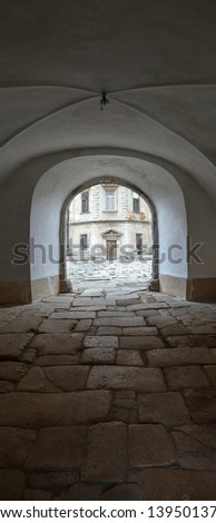 Entrance to the old castle. The road paved with cobblestones. - stock photo