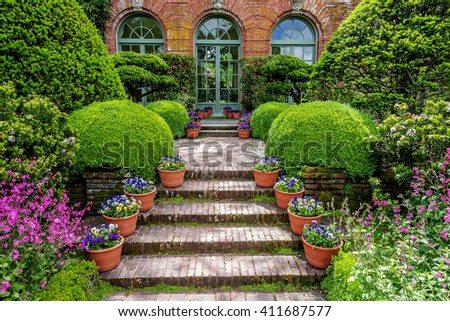 Entranceway from an old English style garden to the side entrance of a 20th century mansion. The brick walkway is lined by potted plants with flowers, rounded hedges, and other lush vegetation. - stock photo