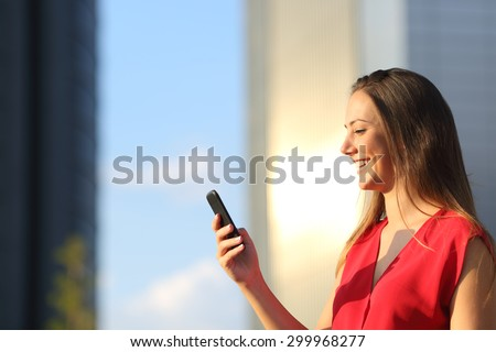 Entrepreneur business woman using a smart phone with office buildings in the background - stock photo