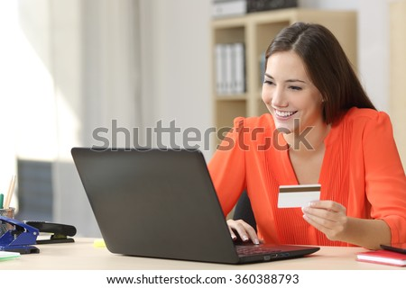 Entrepreneur buying online with a credit card and a laptop in a desk at home or a little office - stock photo