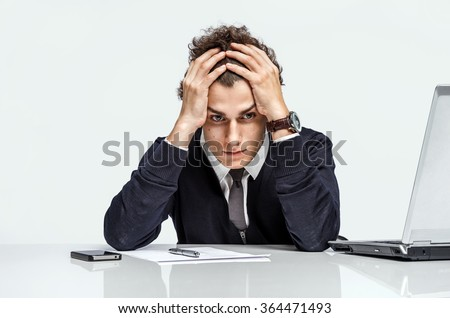 Entrepreneur dissatisfied with his earnings, profit, income, gain, benefit, margin / modern businessman at the workplace working with computer on grey background. Depression and crisis concept - stock photo