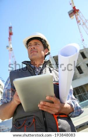 Entrepreneur on building site using tablet - stock photo