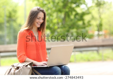 Entrepreneur working with a laptop sitting in a bench in a park - stock photo