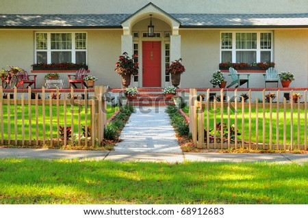 Entryway of a meticulously kept home, with columns, walkway, fence and beautiful landscaping, making this a desirable place to live. - stock photo