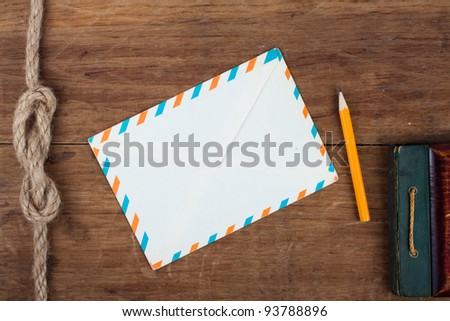 Envelope and pencil on wooden background - stock photo