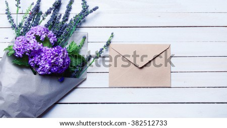 Envelope and wildflowers on white wooden background - stock photo