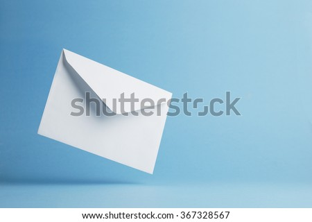 Envelope falling on the ground, blue background with negative space - stock photo