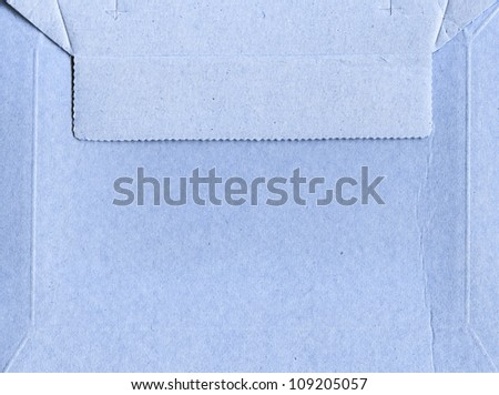 envelope grey blue out of the rough cardboard packaging with the top flap closed - stock photo