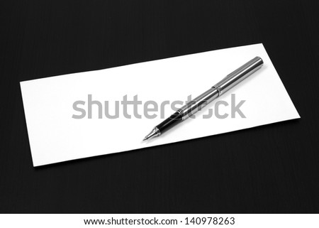envelope on a table with pen - stock photo