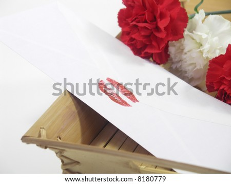 Envelope sealed with lipstick kiss and carnations in the background. Isolated on white with a shallow DOF, focus on lip print. - stock photo