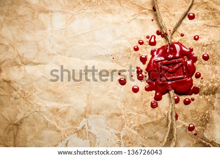 Envelope symbol imprinted in red sealing wax on old paper - stock photo