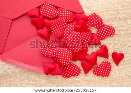Envelope with red hearts on the wooden background - stock photo