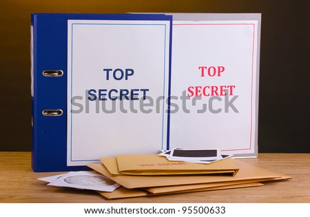 Envelopes and folders with top secret stamp and photo papers with CD disks on wooden table on brown background - stock photo