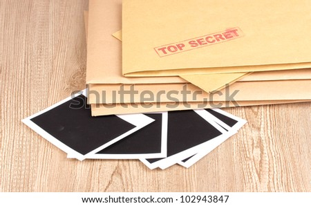 Envelopes with top secret stamp with photo papers close-up on wooden background - stock photo