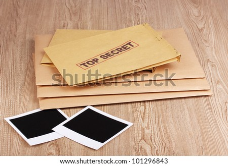 Envelopes with top secret stamp with photo papers on wooden background - stock photo