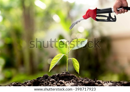 Environment concept saving hand holding fuel nozzle over new life plant blur background - stock photo