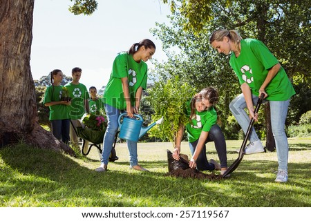 Environmental activists planting a tree in the park on a sunny day - stock photo