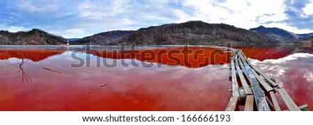 Environmental disaster. Panorama of a lake full with contaminated water from a mine in Geamana, Rosia Montana, Romania  - stock photo