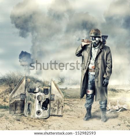 Environmental disaster. Post apocalyptic survivor in gas mask holding axe - stock photo