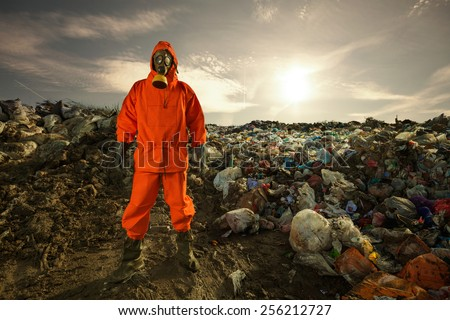Environmental engineer standing on the landfill in front of the municipal waste. - stock photo