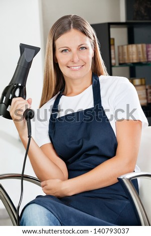 Environmental portrait of confident female hairdresser holding hairdryer at salon - stock photo