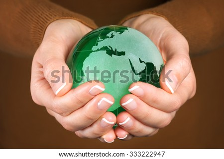 Environmental protection concept with green glass globe in hand - stock photo
