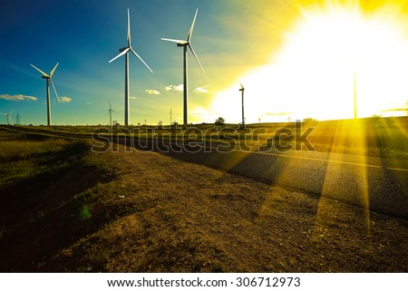Environmentally friendly power generation wind power turbines on the side of dual carriageway road at panoramic - stock photo