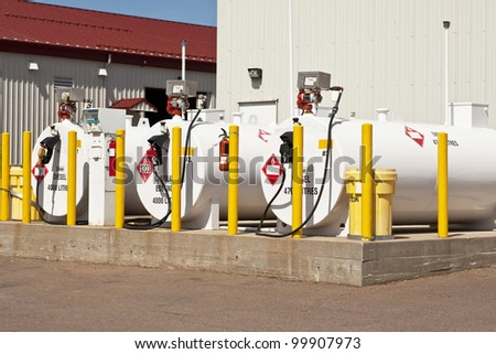 Environmentally safe fuel tanks with safety features such as fire extinguishers and back up pillars to prevent trucks from backing into the tanks. - stock photo