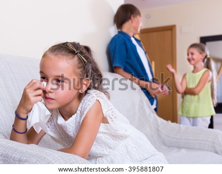 Envy  caucasian child sitting aside of boy and girl at home - stock photo
