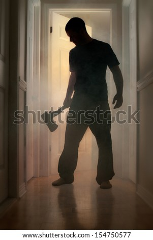 Epic concept with man in silhouette holding axe inside a smoking house at night - stock photo