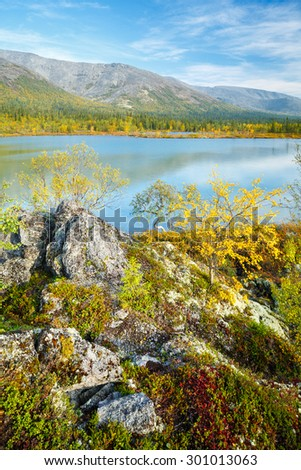 Epic view of Hibiny mountain ridge reflected in azure water of Polygonal lake with birch trees and rocks on the foreground, Kola peninsula above the Arctic Circle, Russia - stock photo