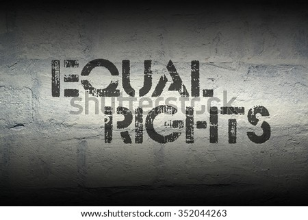 equal rights stencil print on the grunge white brick wall - stock photo