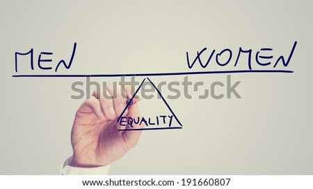 Equality between men and women, a conceptual image of the status of female rights with a man drawing a seesaw on a virtual interface balancing the two concepts on opposite ends in equilibrium.  - stock photo