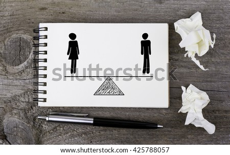 Equality of man and woman. On a wooden table notebook - stock photo