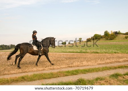 Equestrienne  rides at a gallop across the field. - stock photo