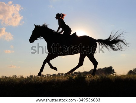 Equetsrian riding her hHorse at sunset - stock photo